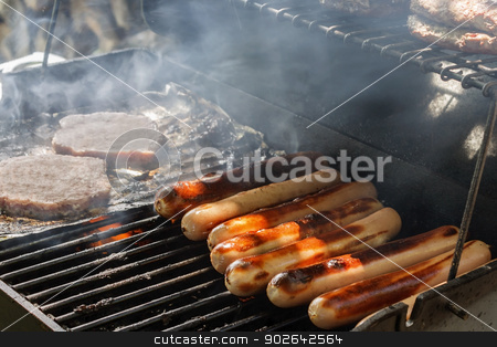Grilling Hotdogs stock photo, Closeup view of grilling hotdogs and hamburgers. by Leah Fallesen