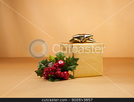 Gold present in Christmas setting stock photo, Gold present and holly isolated over gold by Ulrich Schade