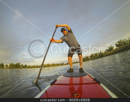 paddling stand up board stock photo, mature male paddler enjoying workout on stand up paddleboard (SUP), calm lake in Colorado, summer by Marek Uliasz