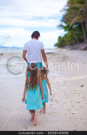 Back view of father and his two little daughters walking by the sea stock photo, Back view of father and his two little daughters walking by the sea by Dmitry Travnikov