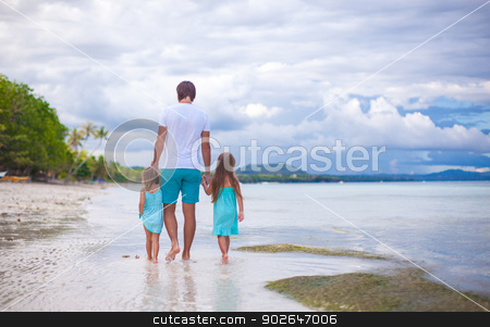 Rear view of father and his two little daughters walking by the sea stock photo, Rear view of father and his two little daughters walking by the sea by Dmitry Travnikov