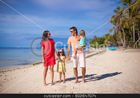 Young beautiful family of four enjoyed relaxing on the beach stock photo, Young beautiful family of four enjoyed relaxing on the beach by Dmitry Travnikov