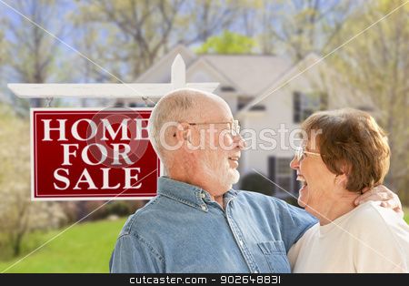 Happy Senior Couple Front of For Sale Sign and House stock photo, Happy Senior Couple Front of For Sale Real Estate Sign and House. by Andy Dean
