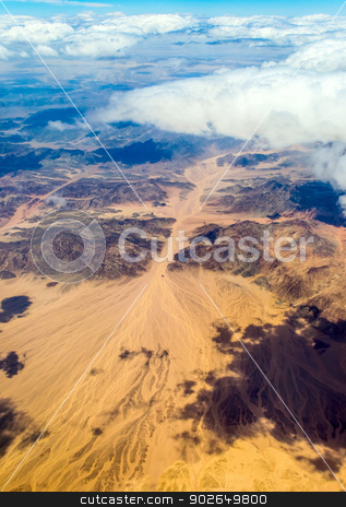 View from the window of an airplane flying stock photo, Aerial view landscape near Hurgada town over clouds in Egypt by Imaster