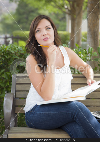 Young Adult Female Student on Bench Outdoors stock photo, Attractive Young Adult Female Student on Bench Outdoors with Books and Pencil. by Andy Dean