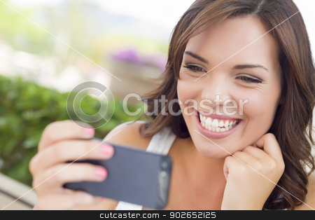 Young Adult Female Texting on Cell Phone Outdoors stock photo, Attractive Smiling Young Adult Female Texting on Cell Phone Outdoors on a Bench. by Andy Dean
