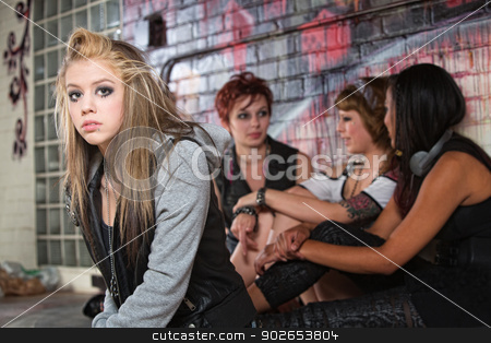 Depressed Teen with Friends stock photo, Teenager with low self-esteem near three friends by Scott Griessel