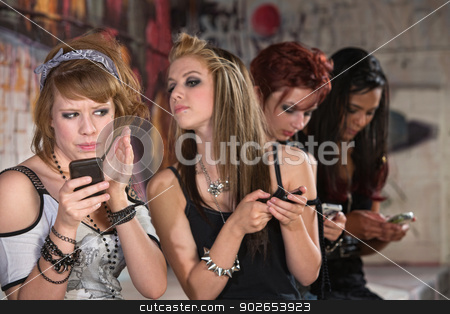 Female Teen Hiding Phone stock photo, Annoyed teenager hiding phone from nosey girl by Scott Griessel