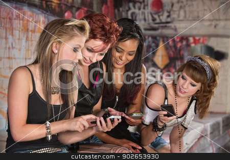Girls Sharing Cellphone Information stock photo, Group of beautiful teenage females looking at their phones by Scott Griessel