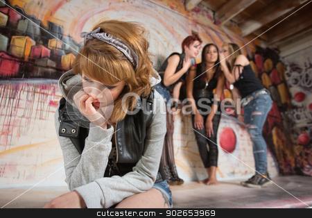 Sad Teenager Sitting Alone stock photo, Three women talking about sad teenager sitting alone by Scott Griessel