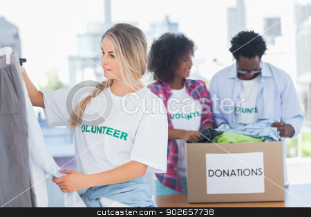 Volunteers putting clothes in clothes rail stock photo, Volunteers putting clothes in clothes rail in their office by Wavebreak Media