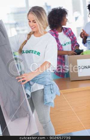 Smiling volunteers putting clothes in clothes rail stock photo, Smiling volunteers putting clothes in clothes rail in their office by Wavebreak Media
