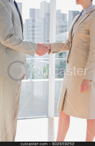 Business team shaking hands stock photo, Business team shaking hands by large windows by Wavebreak Media