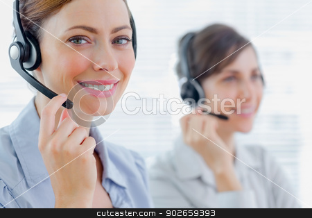 Smiling call centre agents with headsets at work stock photo, Smiling call centre agents with headsets at work in an office by Wavebreak Media