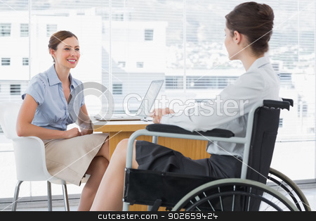 Businesswoman speaking with disabled colleague stock photo, Businesswoman speaking with disabled colleague at desk in office by Wavebreak Media