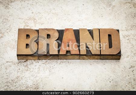 brand word in wood type stock photo, brand word in vintage letterpress wood type on a ceramic tile background by Marek Uliasz