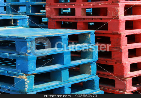 Colorful stacks of crate pallets stock photo, Colorful stacks of red and white crate pallets. by Martin Crowdy