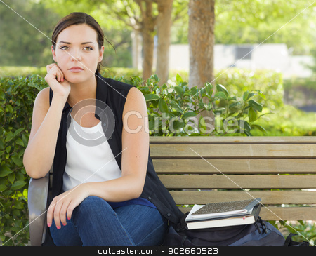 Melancholy Young Adult Woman Sitting on Bench Next to Books stock photo, Melancholy Young Adult Woman Sitting on Bench Next to Books and Backpack. by Andy Dean