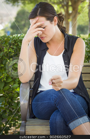 Upset Young Woman Sitting Alone on Bench stock photo, Upset Young Woman Sitting Alone on Bench Outside with Her Head in Her Hand and Clinched Fist. by Andy Dean