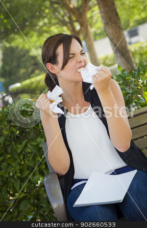 Upset Young Woman with Pencil and Crumpled Paper in Hands stock photo, Frustrated and Upset Young Woman with Pencil and Crumpled Paper in Her Hand Sitting on Bench Outside. by Andy Dean