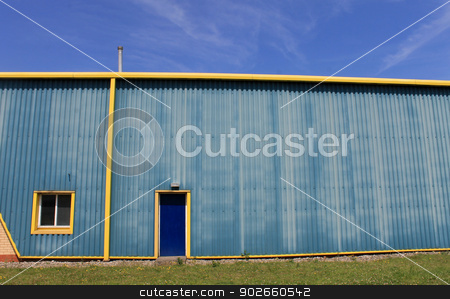 Industrial warehouse building stock photo, Exterior of industrial warehouse building in blue and yellow. by Martin Crowdy