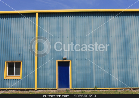 Yellow warehouse building stock photo, Exterior of large modern yellow and blue warehouse building. by Martin Crowdy