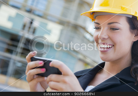 Female Contractor Wearing Hard Hat on Site Texting with Phone stock photo, Young Professional Female Contractor Wearing Hard Hat at Contruction Site Texting with Cell Phone. by Andy Dean