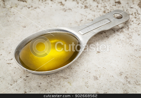 tablespoon of olive oil stock photo, Measuring tablespoon of olive oil on a kitchen counter (ceramic tile) by Marek Uliasz
