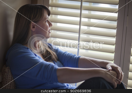 Pensive Woman Sitting Near Window Shades stock photo, Pensive Woman Calmly Sitting Near Window Shades. by Andy Dean