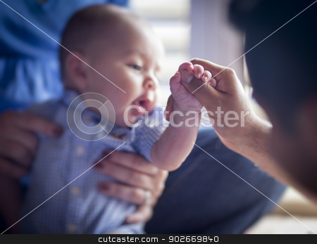 Cute Mixed Race Infant Boy Holds Father's Thumb stock photo, Cute Mixed Race Infant Holds Father's Thumb as Mom Looks On - Focus is on the Hand of the Baby Boy. by Andy Dean
