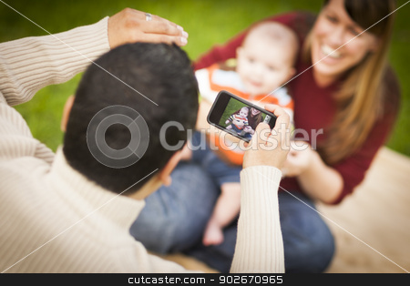 Happy Mixed Race Parents and Baby Boy Taking Self Portraits stock photo, Happy Mixed Race Parents and Baby Boy Taking Self Portraits Outside at the Park. by Andy Dean