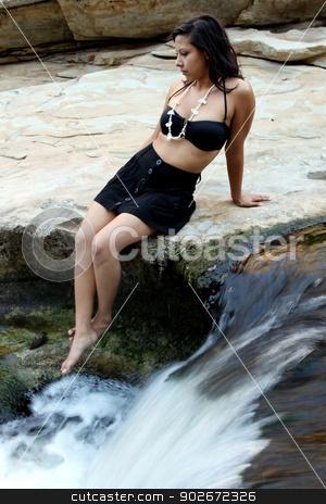 Hispanic Woman Waterfall stock photo, Hispanic woman with bikini sitting next to a waterfall. by Henrik Lehnerer