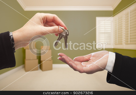Woman Handing Over the House Keys Inside Empty Green Room stock photo, Woman Handing Over the House Keys To A New Home Inside Empty Green Colored Room. by Andy Dean