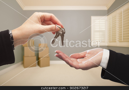 Woman Handing Over the House Keys Inside Empty Grey Room stock photo, Woman Handing Over the House Keys To A New Home Inside Empty Grey Colored Room. by Andy Dean