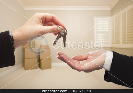 Woman Handing Over the House Keys Inside Empty Tan Room stock photo, Woman Handing Over the House Keys To A New Home Inside Empty Tan Colored Room. by Andy Dean