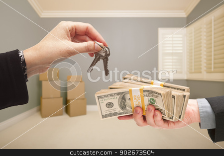 Handing Over Cash For House Keys stock photo, Man and Woman Handing Over Cash For House Keys Inside Empty Gray Room with Boxes. by Andy Dean