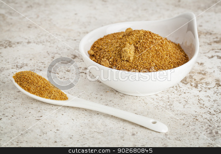 coconut palm sugar stock photo, small ceramic bowl of unrefined coconut palm sugar against a ceramic tile background with a spoon by Marek Uliasz