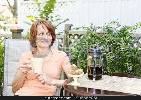 Woman relaxing in backyard stock photo, Happy woman relaxing with coffee and cookies on deck chair in backyard at home by Elena Elisseeva