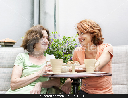 Mother and daughter relaxing in backyard stock photo, Mature women relaxing and talking with coffee on patio in backyard at home by Elena Elisseeva
