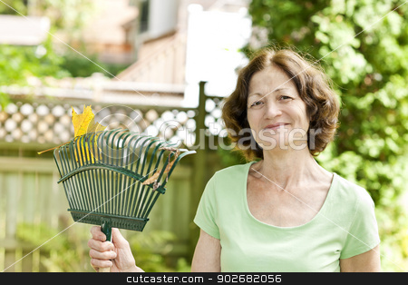 Senior woman holding rake stock photo, Senior woman smiling holding rake for yard work outside by Elena Elisseeva