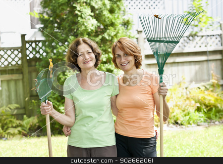 Women with rakes in garden stock photo, Mother and daughter holding rakes gardening doing yard work outside by Elena Elisseeva