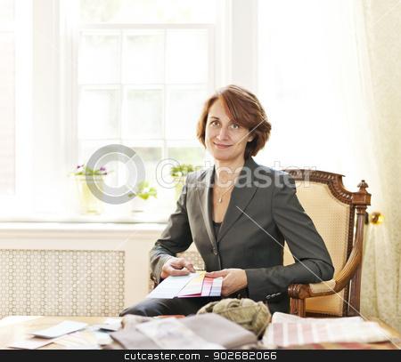 Female interior designer stock photo, Female interior designer with color samples sitting at desk by Elena Elisseeva