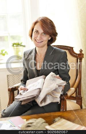 Female interior designer stock photo, Female interior designer with fabric samples sitting at desk by Elena Elisseeva