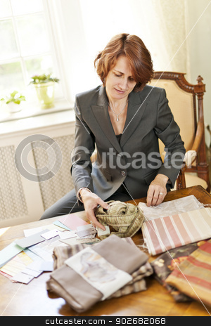 Female interior designer stock photo, Female interior designer choosing from fabric samples sitting at desk by Elena Elisseeva