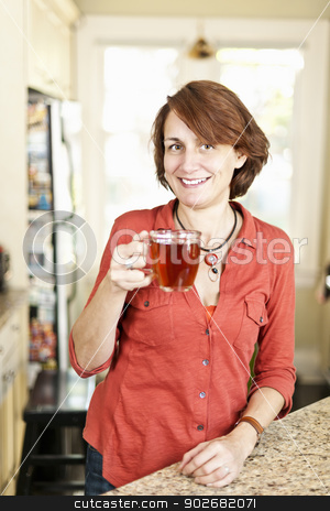 Smiling woman with tea at home stock photo, Smiling mature woman holding cup of tea in kitchen at home by Elena Elisseeva