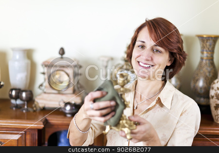 Woman polishing antiques stock photo, Happy caucasian woman proudly polishing antique collection by Elena Elisseeva