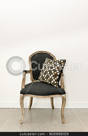 Antique armchair near wall stock photo, Antique armchair furniture with cushion against white wall by Elena Elisseeva