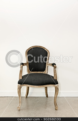 Antique armchair near wall stock photo, Antique upholstered armchair furniture against white wall by Elena Elisseeva