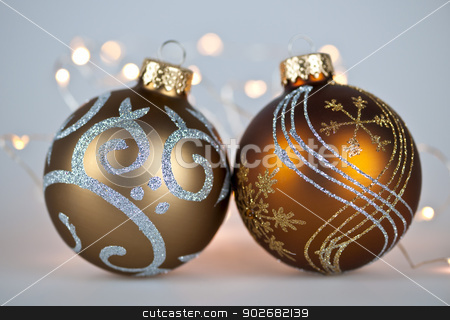 Golden Christmas ornaments stock photo, Two gold Christmas decorations with decorative lights on gray background by Elena Elisseeva