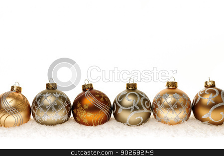 Row of gold Christmas ornaments stock photo, Row of golden Christmas balls with festive designs on snow by Elena Elisseeva